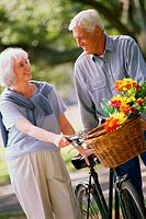 Senior couple standing with a bicycle