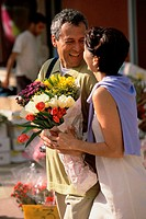 Couple smiling holding a bouquet of flowers