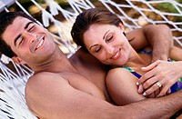 Young couple lying together on a hammock