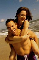Young woman riding piggyback on a young man at the beach