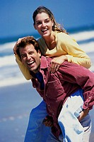 Portrait of a young woman riding piggyback on a young man at the beach