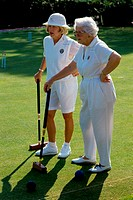 Two senior women standing on a lawn holding croquet mallets