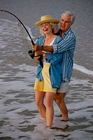 Senior couple fishing together on the beach