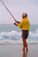 Senior man fishing on the beach