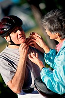 Woman helping a man put on a cycling helmet