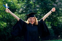 Portrait of a young woman wearing a graduation outfit holding a diploma (thumbnail)