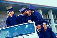 Group of graduating students sitting in an all terrain vehicle
