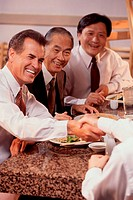 Three business executives seated at a restaurant