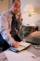 Businessman writing in a book while talking on a telephone
