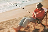 Senior man sitting on a beach chair with a fishing rod
