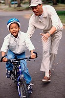 Young man teaching his son to ride a bicycle