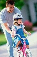 Man helping his daughter learn to ride a bicycle