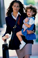 Portrait of a businesswoman carrying her daughter