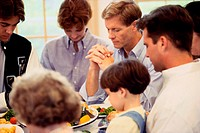 Members of a family praying at the dinner table