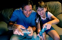 Father and daughter playing a video game together