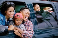 Family together in a vehicle looking out smiling
