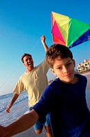 Close-up of a boy flying a kite with his father on the beach