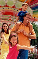 Young couple at an amusement park with their son and daughter