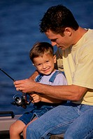 Father and son fishing from a boat