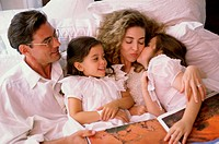Father and mother lying in bed with their two daughters