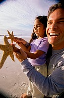 Close-up of a man showing his daughter a starfish on the beach