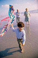 Boy flying a kite on the beach with his grandparents