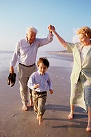 Boy playing on the beach with his grandparents