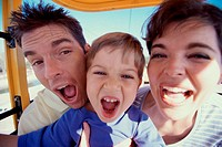 Close-up of a couple on an amusement park ride with their son