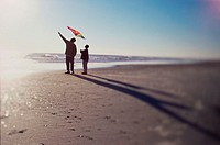 Silhouette of a father and son flying a kite on the beach