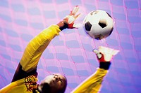 Low angle view of a goalie catching a ball