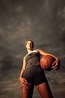 Low angle view of a young woman holding a basketball