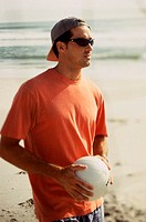 Young man holding a volleyball on the beach