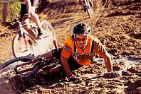 Young man falling from a bicycle in a race
