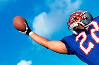 Low angle view of an American football player catching a ball