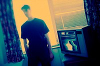 Young man standing beside a television