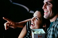 Close-up of a young couple watching a movie in a theater