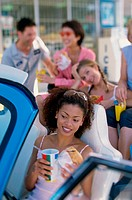 Group of young men and women eating fast food in a car