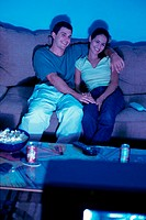 Young couple sitting on a couch and watching television