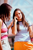 Two teenage girls talking on a mobile phone
