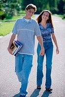 Teenage couple holding hands walking outdoors