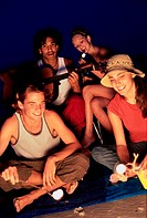 Two young couples sitting by a bonfire on the beach