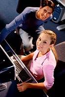 Portrait of a young man and a young woman sitting in a computer class