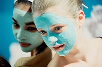 Close-up of two teenage girls wearing facial masks