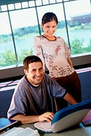 Portrait of a young man sitting in front of a laptop with a young woman standing behind him