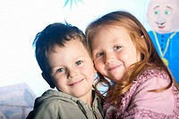 Close up headshot of 4 year old girl and 3 year old boy, smiling into camera