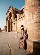 Caretaker rests on column at Kom Ombo, Temple of Horus and Sobek. Kom Ombo, Egypt