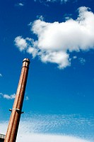 Old smokestack and cloud as smoke