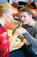 A young couple sitting in a cafe sharing a bowl of fruit smiling