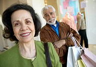 Portrait of a Mature Couple Shopping, the Bored Man in the Background Carrying Shopping Bags