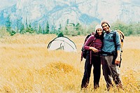 Young, Happy Couple With Rucksacks Stand Side by Side in a Field in Front of Their Tent